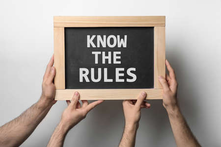 Men holding chalkboard with phrase Know the rules on white background, closeup Archivio Fotografico
