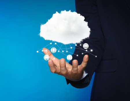Modern storage technology concept. Man demonstrating cloud with icons on light blue background, closeup