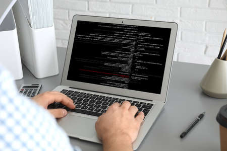 Professional programmer working with laptop in office, closeup