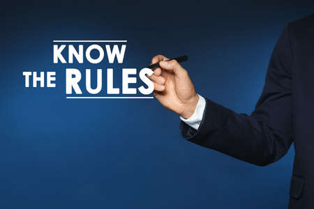 Businessman using virtual screen with phrase Know the rules, closeup