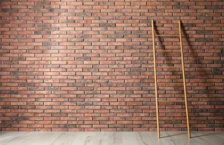 Modern wooden ladder near brick wall. Space for text