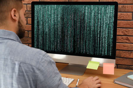 Professional programmer working with computer in office, closeup