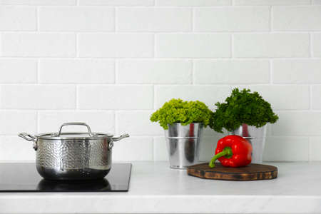 Kitchen counter with products and saucepot on stove Foto de archivo