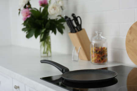 Crepe pan on induction stove in kitchen Stock Photo