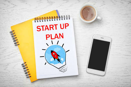 Notebook with phrase START UP PLAN, smartphone and cup of coffee on light wooden background, flat lay