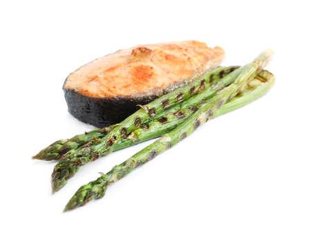 Tasty salmon steak with asparagus isolated on white