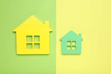 Small and big house figures on color background, flat lay. Pareto principle concept