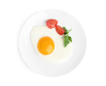 Tasty fried egg with parsley and tomato isolated on white, top view
