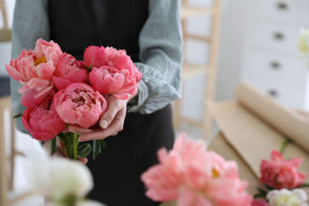 Florist with beautiful peony bouquet indoors, closeup