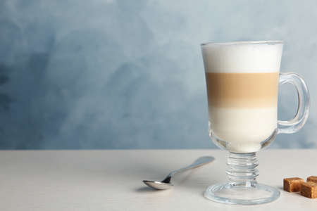 Delicious latte macchiato and sugar cubes on white table against light blue background, space for text