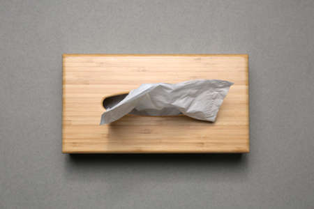 Holder with paper tissues on grey background, top view