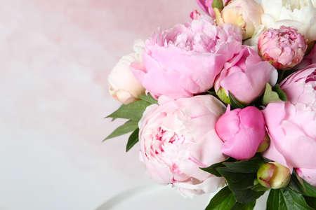 Ramo de hermosas peonías sobre fondo rosa, primer plano