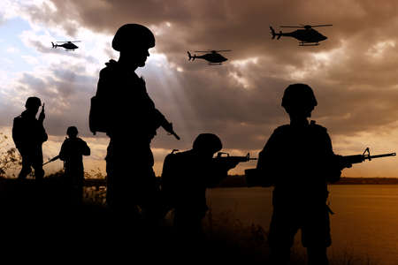 Silhouettes of soldiers with assault rifles and military helicopters patrolling outdoors Banque d'images