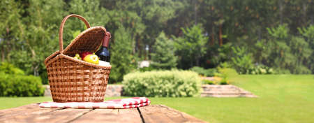 Picnic basket with fruits, bottle of wine and checkered blanket on wooden table in garden, space for text. Banner design