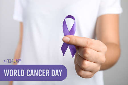 Woman holding purple ribbon against grey background, closeup. World Cancer Day