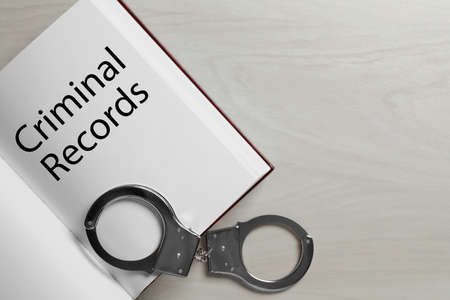 Book with words CRIMINAL RECORDS and handcuffs on white wooden background, top view. Space for text