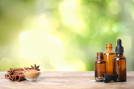 Bottles of essential oil, cinnamon sticks and powder on wooden table against blurred background. Space for text