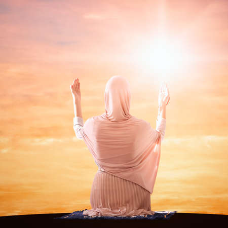 Muslim woman in traditional clothes praying at sunrise, back view. Holy month of Ramadan