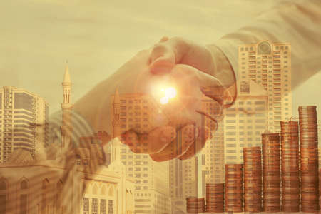 Multiple exposure of partners shaking hands, stacked coins and cityscape, closeup. Business corporation
