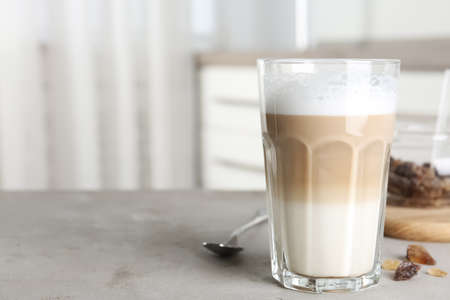 Delicious latte macchiato on grey table indoors, space for text