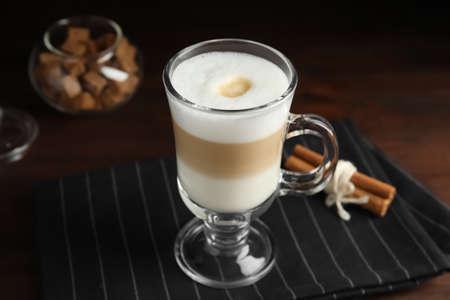Delicious latte macchiato and cinnamon on table
