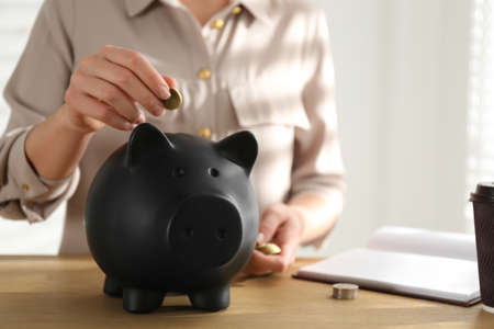 Woman putting money into piggy bank at wooden table indoors, closeup