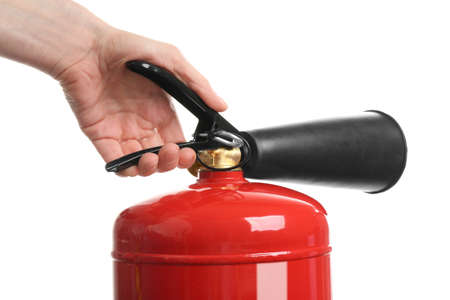 Woman using fire extinguisher on white background, closeup