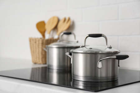 New saucepots on induction stove in kitchen Stock Photo