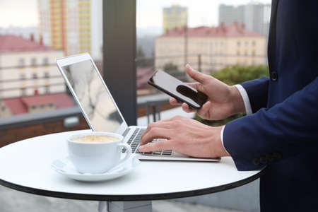 Businessman with laptop and mobile phone in outdoor cafe, closeup. Corporate blog