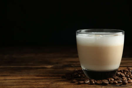 Delicious latte macchiato and coffee beans on wooden table against black background, space for text