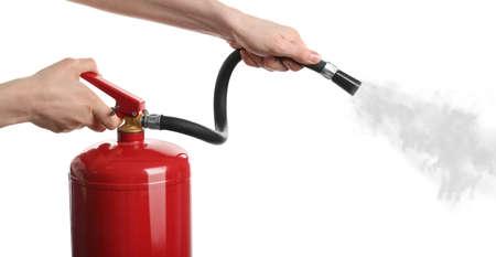 Woman using fire extinguisher on white background, closeup Standard-Bild