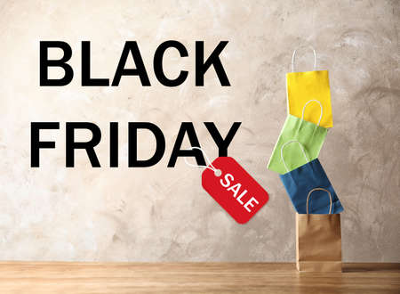 Colorful shopping bags and text BLACK FRIDAY SALE on beige background