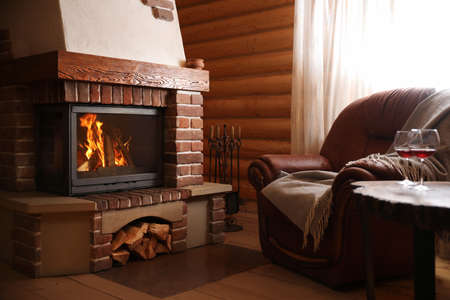 Modern cottage interior with stylish furniture and fireplace. Winter vacation