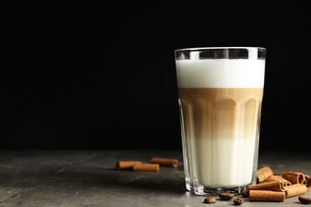 Delicious latte macchiato and cinnamon on grey table against black background, space for text Reklamní fotografie