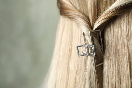 Young woman with beautiful hair claw on grey background, closeup