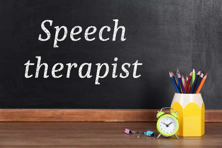 Pencils, alarm clock and text Speech Therapist written on blackboard