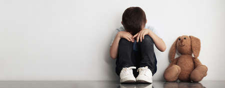 Sad little boy sitting near white wall, banner design with space for text. Time to visit child psychologist Фото со стока