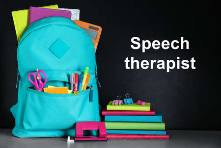 Bright backpack with school stationery and text Speech Therapist on chalkboard