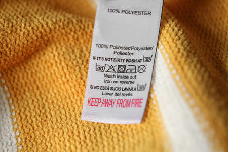 Clothing label with care symbols and material content on yellow shirt, closeup view Stockfoto