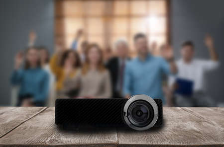 Modern video projector and blurred people on background Foto de archivo