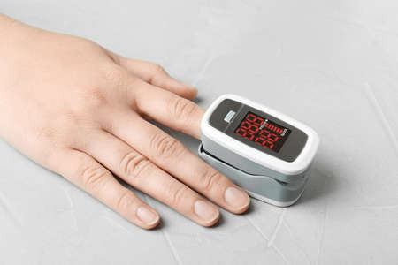 Woman using fingertip pulse oximeter on light grey stone background, closeup