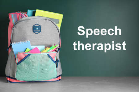 Stylish backpack with school stationery and text Speech Therapist on chalkboard  Фото со стока