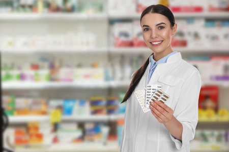 Professional pharmacist with pills in modern drugstore, space for text