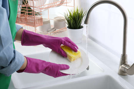 Woman washing plate in modern kitchen, closeup