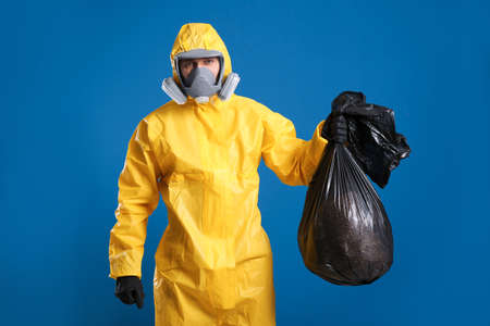 Man in chemical protective suit holding trash bag on blue background. Virus research