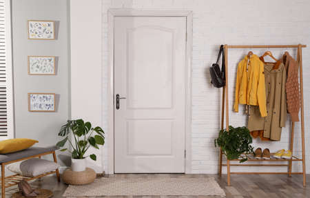 Hallway interior with stylish furniture, clothes and plants