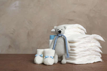 Baby diapers, toy bear and child's booties on wooden table. Space for text Banque d'images