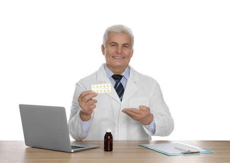 Professional pharmacist with pills and laptop at table against white background