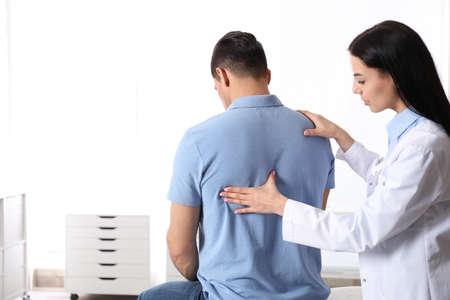 Professional orthopedist examining man in medical office