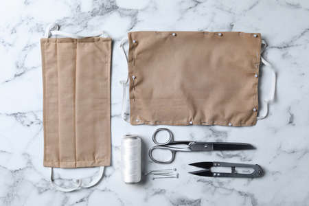 Homemade protective masks and sewing accessories on white marble background, flat lay